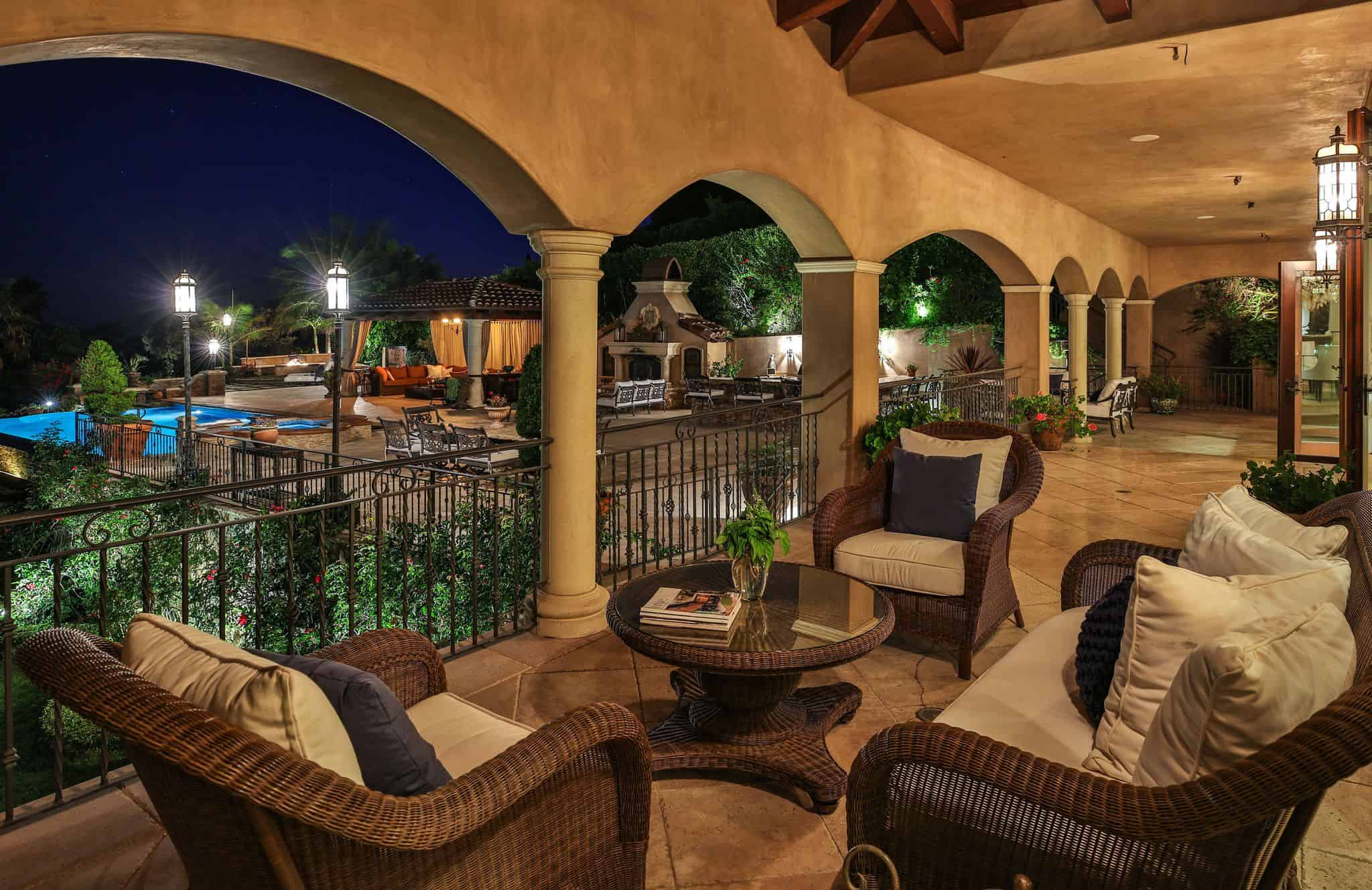 Night time view of the mansion's balcony patio overlooking the beautiful backyard.