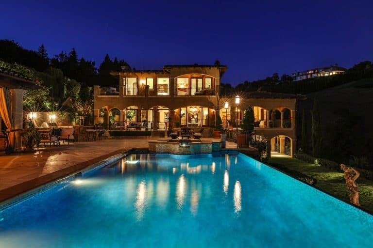 Night time view of the swimming pool area showcasing the beautiful lighting and structure of the mansion.