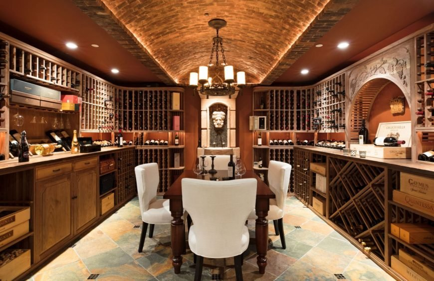 Luxurious wine cellar lighted by a rustic chandelier that hung over a barrel vault ceiling. It has a rectangular tasting table in the middle with white upholstered chairs.