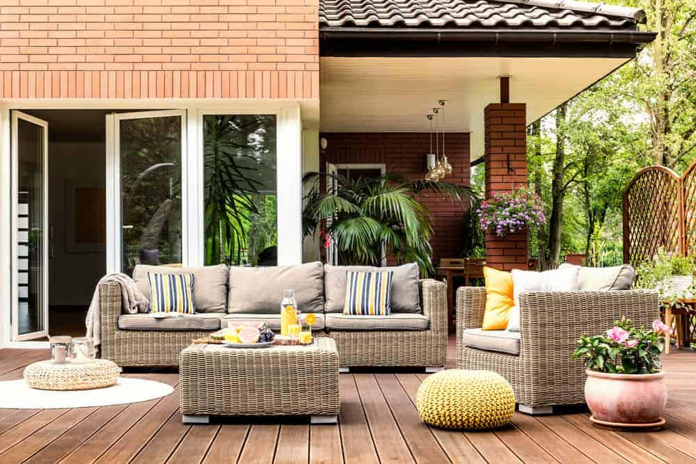 This deck offers a of a set of rattan sofa with an ottoman on the center. The seats are equipped with foam seats and back rests. Additional designs such as footrest and a plant add colors to the deck.