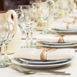 Long formal dining table with table settings on white tablecloth