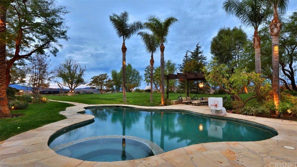 The pool features a customized shape surrounded by mature trees and features a pergola.