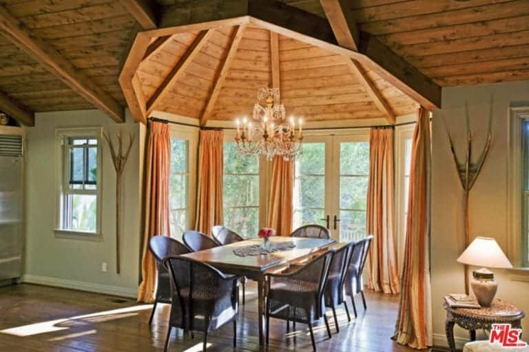 Warm dining room illuminated by an elegant chandelier that hung from the dome ceiling lined with wood beams. It has a french door and windows covered with coral draperies.