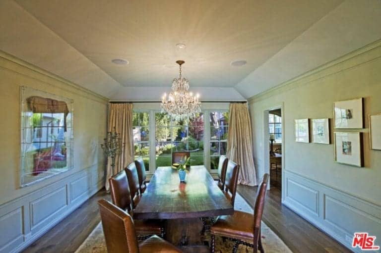 This dining room is decorated with gorgeous picture frames mounted above the white wainscoting. It has a wooden dining table surrounded with brown leather chairs on an area rug.
