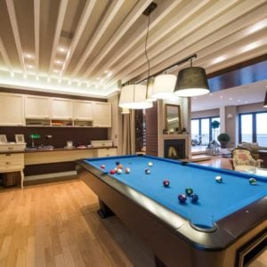 Large game room with pool table with blue felt in room with light hardwood flooring