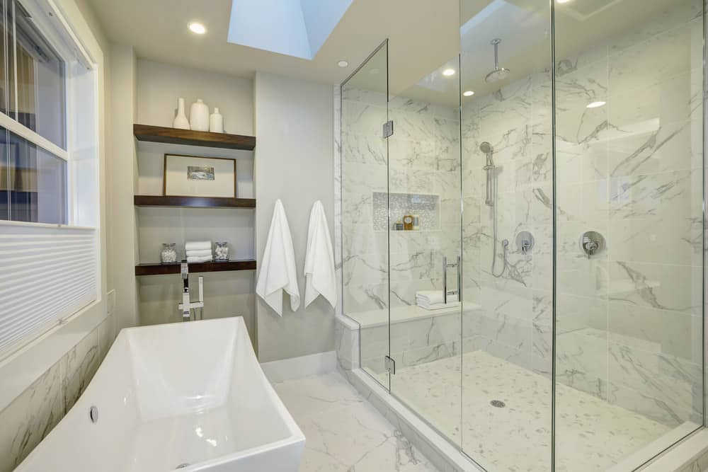 White marble dominates this master bath giving it a bright widening look while the solid glass paneling enclose a grandiose sized shower with a ceiling mounted chrome shower head. A built in full length bench in the shower and a second chrome handheld shower head provide at your fingertips convenience while showering. A free standing rectangular white ceramic tub utilizes the remaining space in the bathroom well.