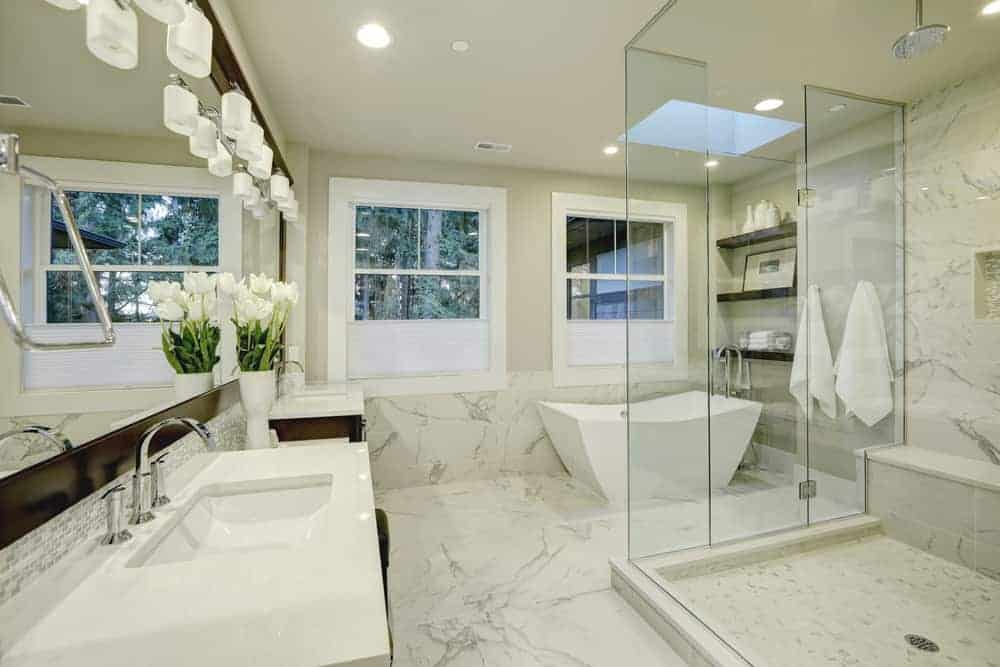 A gorgeous primary bathroom featuring a smooth white marble flooring and a stunning freestanding tub. There's a walk-in shower and large sinks with white countertops.