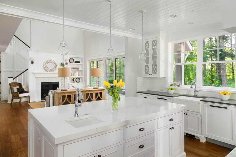 White Mediterranean kitchen featuring a hardwood flooring, a center island with a smooth white marble countertop lighted by pendant lights and french windows.