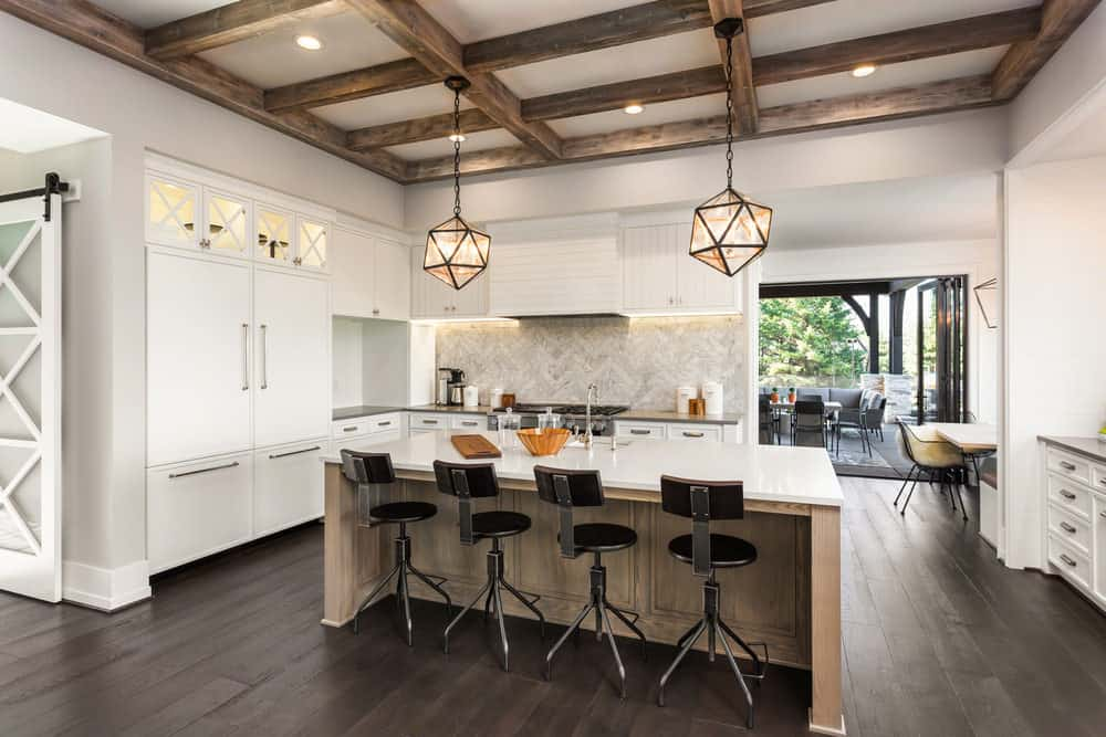 Rustic kitchen with rustic pendant lights and wood-beamed ceiling.