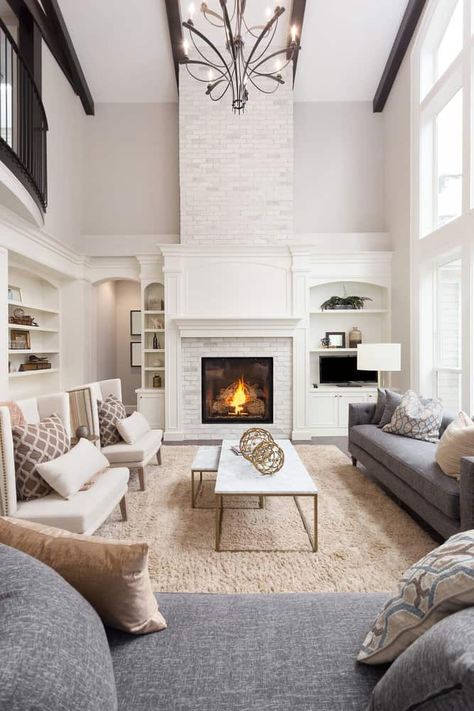 2-story white living room with fireplace and stylish, comfortable furniture.