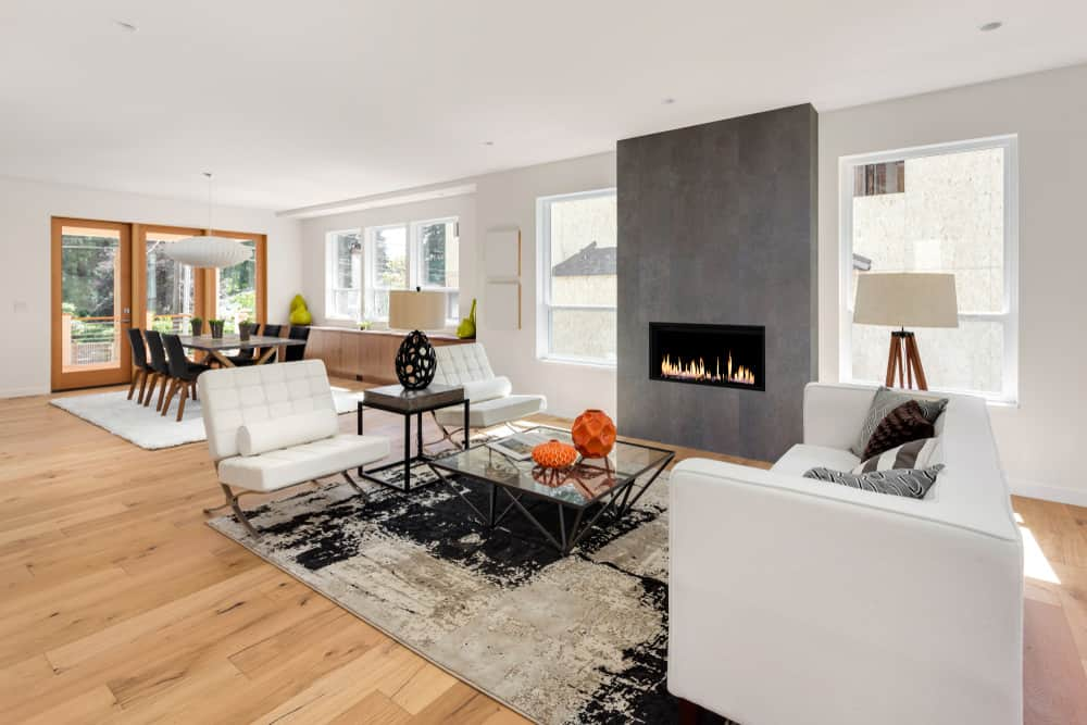 Contemporary living room with gray fireplace and white sofas.