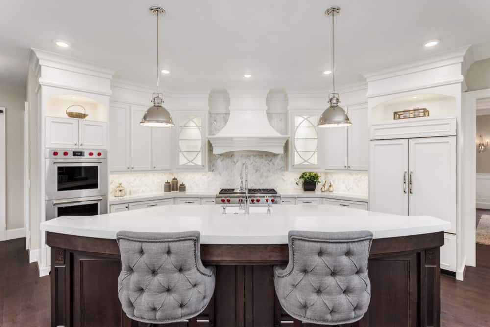 Elegant crisp white kitchen with island and gray tufted bar stools.