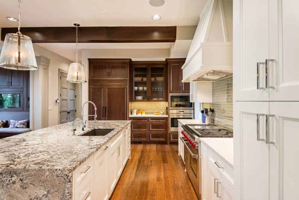 Large Mediterranean kitchen with hardwood flooring and brown cabinetry. There's a large center island with marble countertop lighted by a couple of pendant lights.