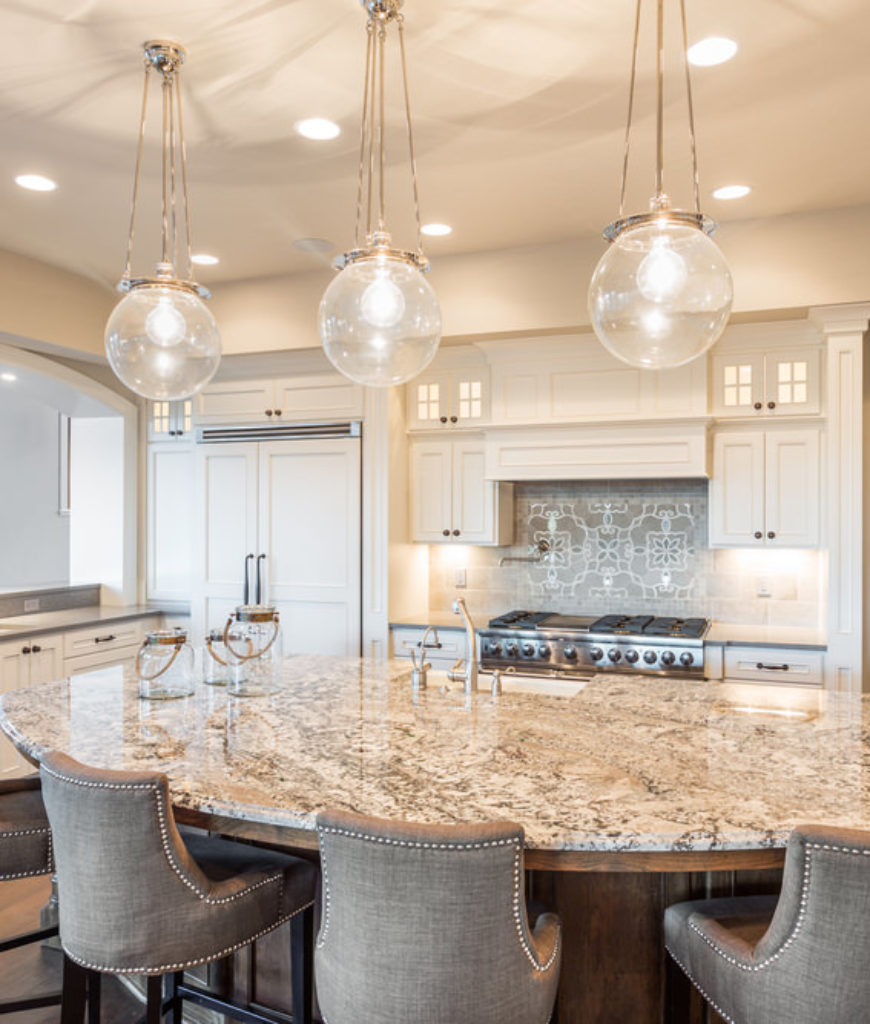 Elegant white kitchen with large breakfast nook at the island and round ball pendant lights.