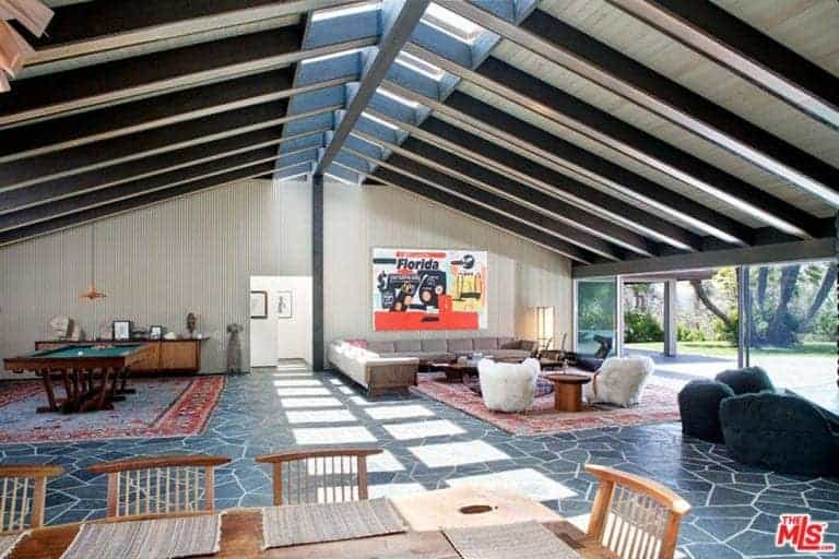 A sprawling great room featuring very attractive floors and a staggering vaulted ceiling.
