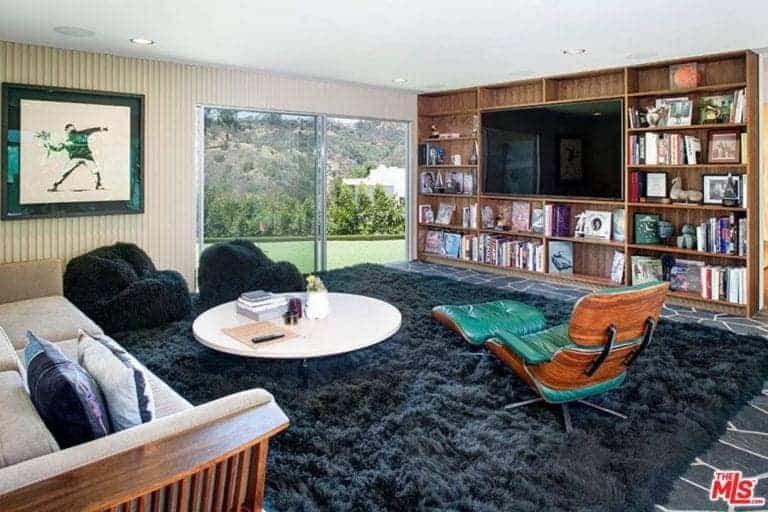 A flat panel TV is fitted to the built-in shelving in this living room decorated with a wall art that's mounted on the beadboard wall. It includes a beige sofa and round coffee table along with black comfy chairs and a green lounge chair over the shaggy rug.
