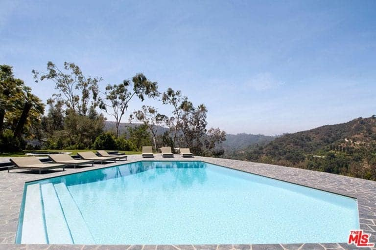 The custom swimming pool boasts multiple sitting lounge while also mirroring the beautiful Beverly Hills skies.