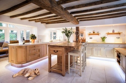 Large kitchen area featuring two wooden islands, with one serves as a breakfast bar. The area also features tiles flooring and a ceiling with exposed beams.