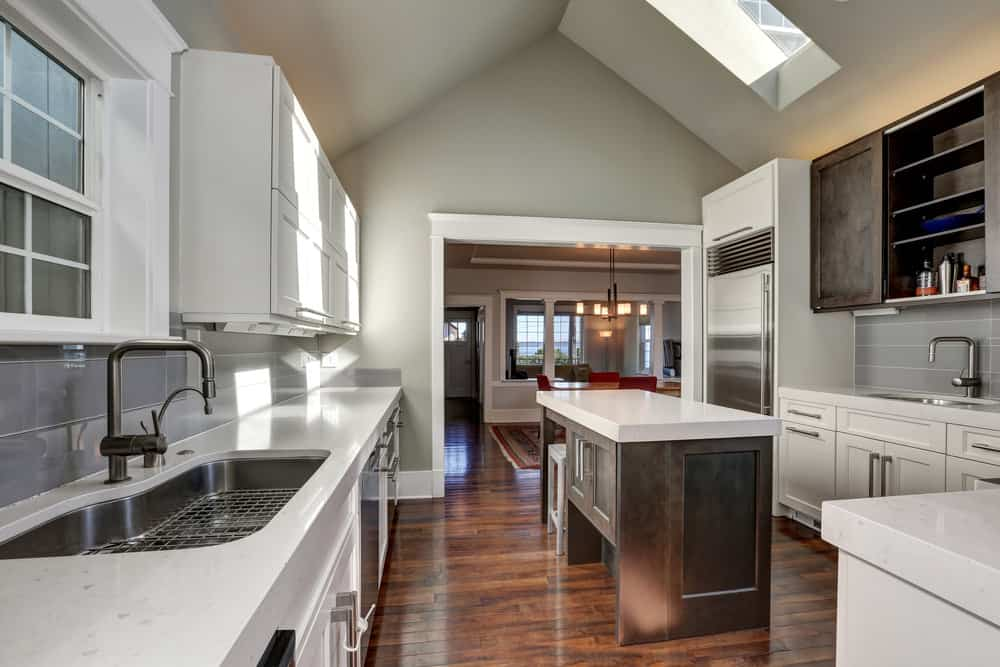 This kitchen has a vaulted ceiling with a skylight. The hardwood flooring looks good with the white ceiling and smooth counters. There's also a narrow center island.