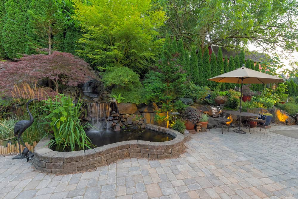 Large brick patio surrounded by gardens, trees and bushes along with a gorgeous pond.
