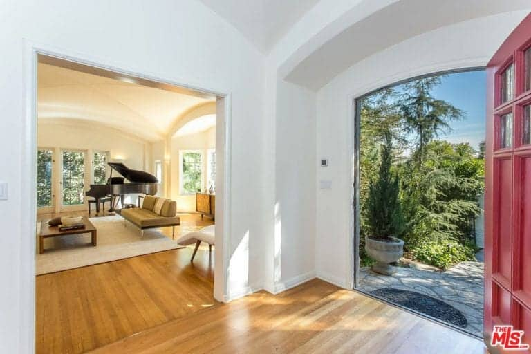 The large entry has a vaulted ceiling and hardwood flooring along with white walls and red French door.