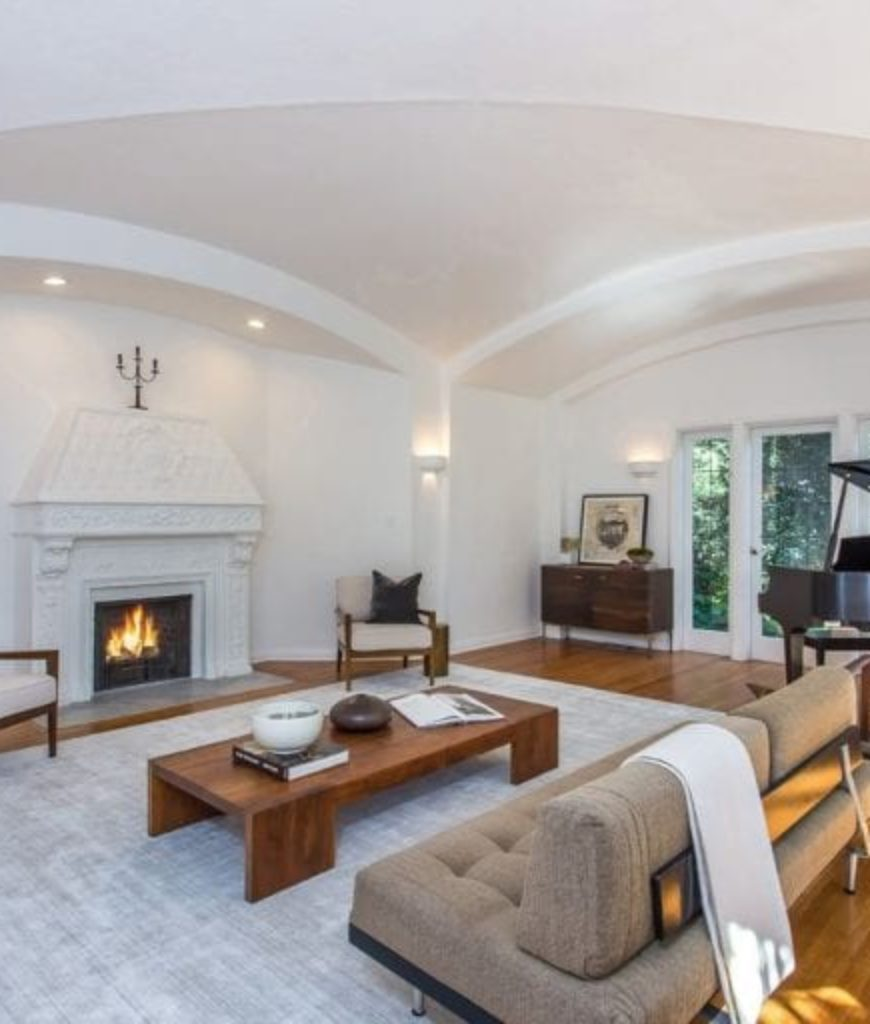 The formal living room offers a cozy fireplace and a grand piano with a nice elegant rug and well-placed lighting.