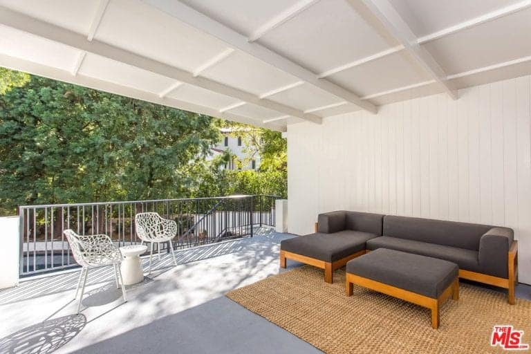 The balcony patio offers additional seating lounge with a coffered ceiling and white walls along with a nice sofa seating.