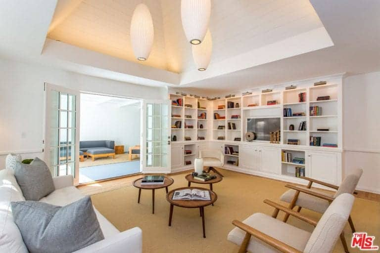 This living room offers a nice set of seats and coffee tables. There are several shelves with books. This room is perfect for spending time reading books.
