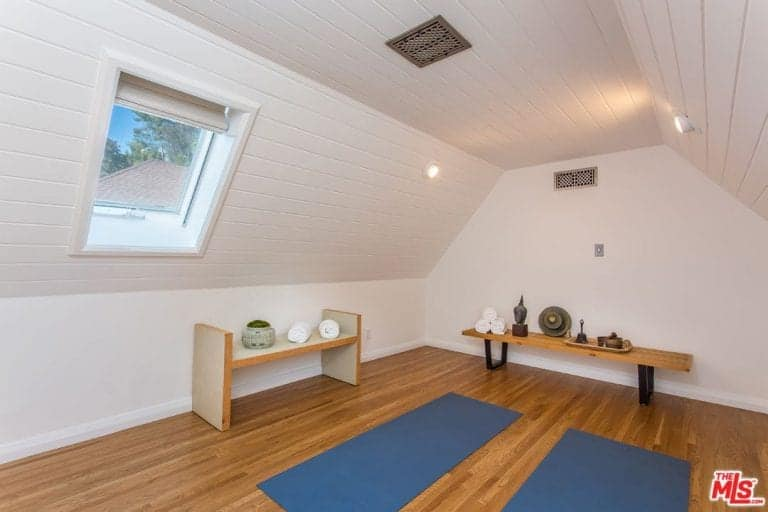 The yoga room provides relaxation spot inside the house. White walls cover the entire room lighted by recessed lights.
