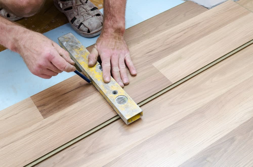 Lever tool used with a pencil for measurement on hardwood flooring.