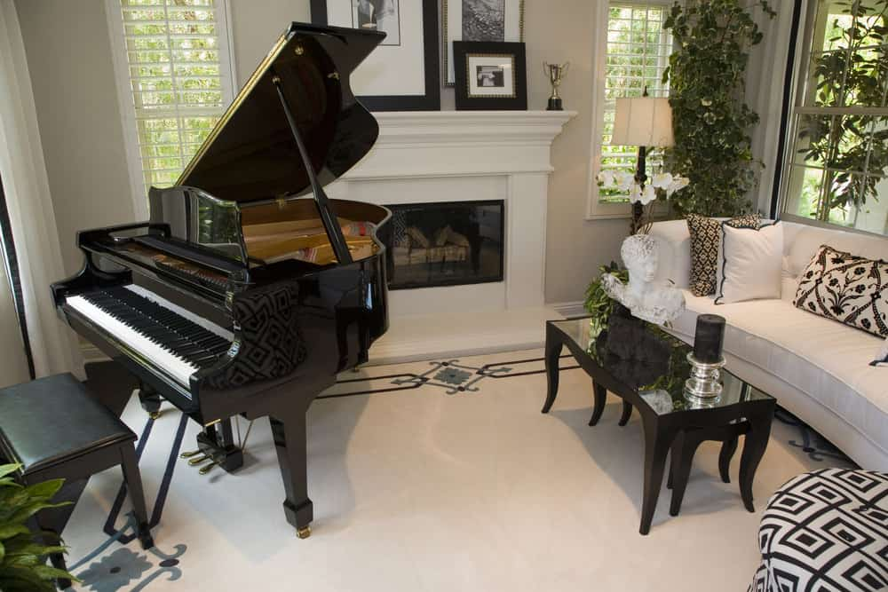 Cozy living room with white flooring, white fireplace and black baby grand piano.