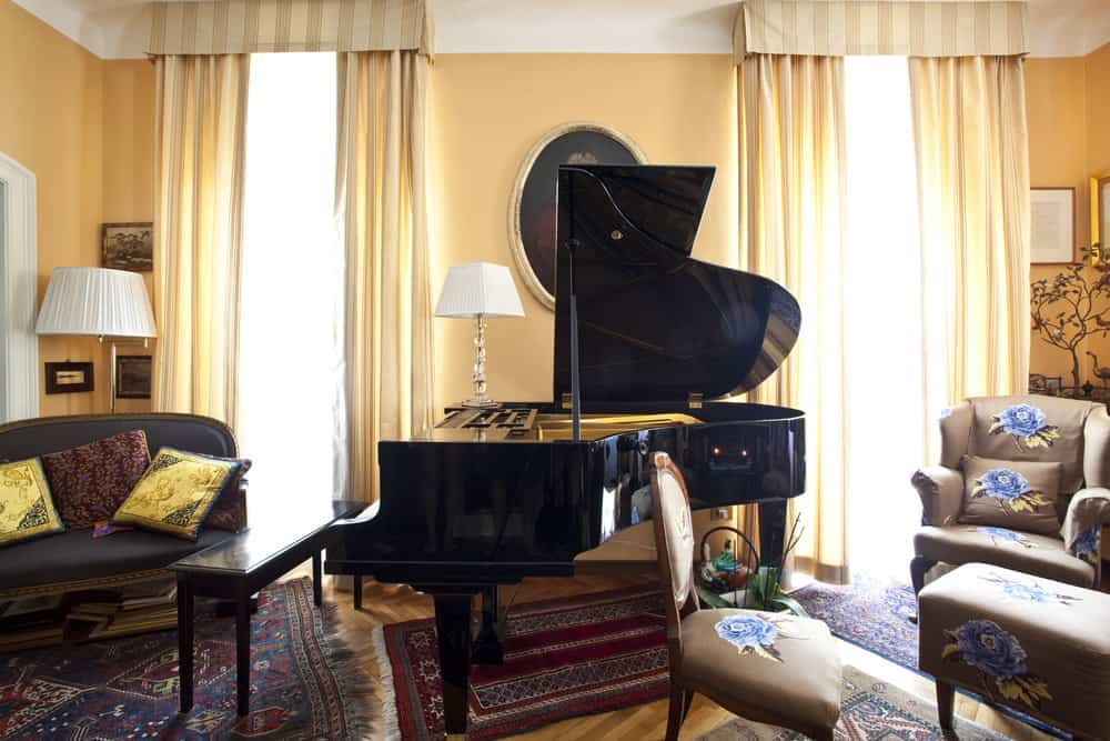 Cozy music room with grand piano. Gorgeous curtains hanging on the windows.
