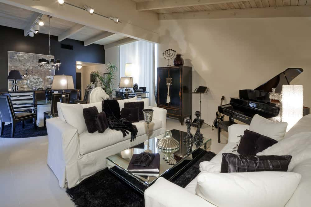 Cozy formal living room with two white sofas, black throw pillows and black baby grand piano.