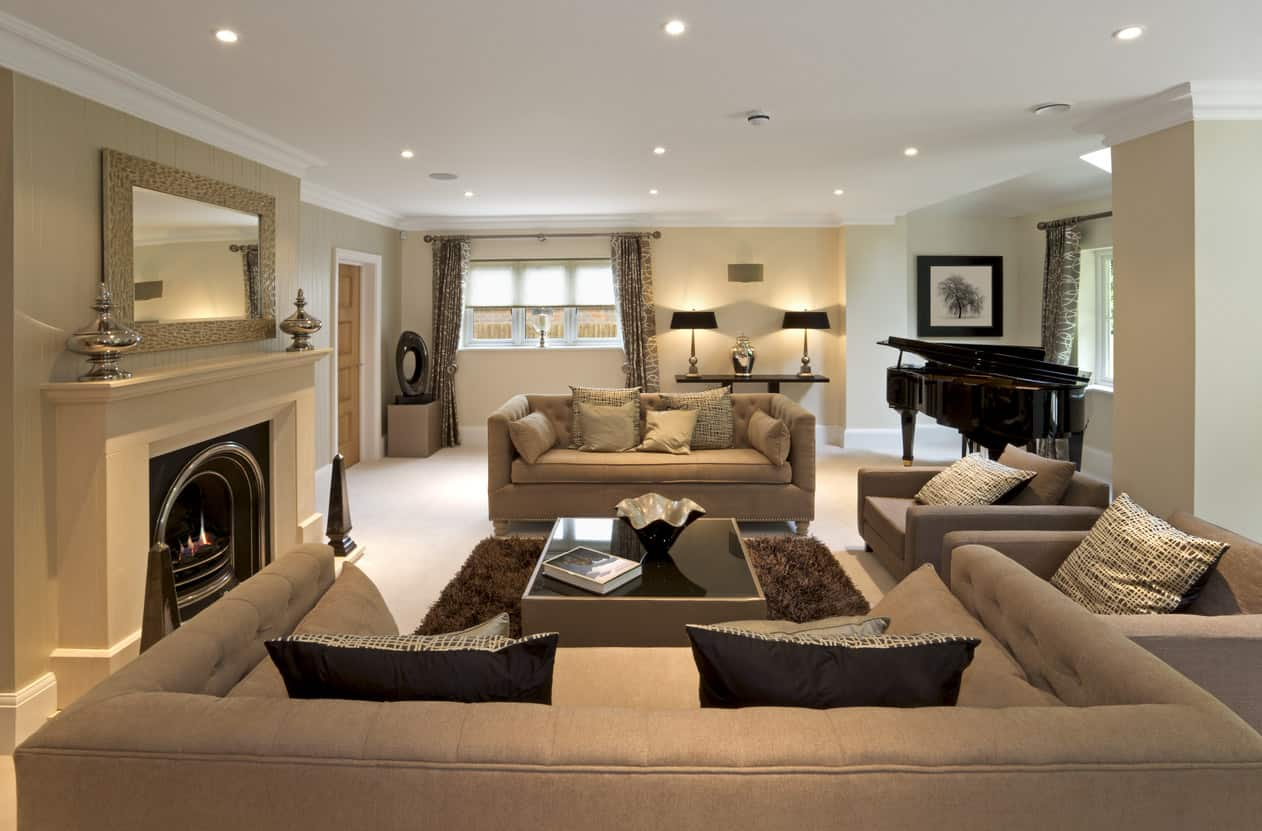Lounge-like living room with brown sectional sofa, fireplace, recessed lighting and black grand piano.