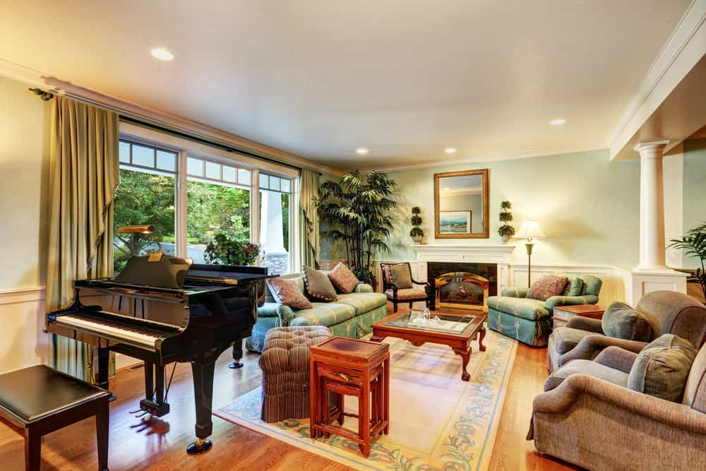 Large living room with area rug, green accent wall and baby grand piano in the corner.