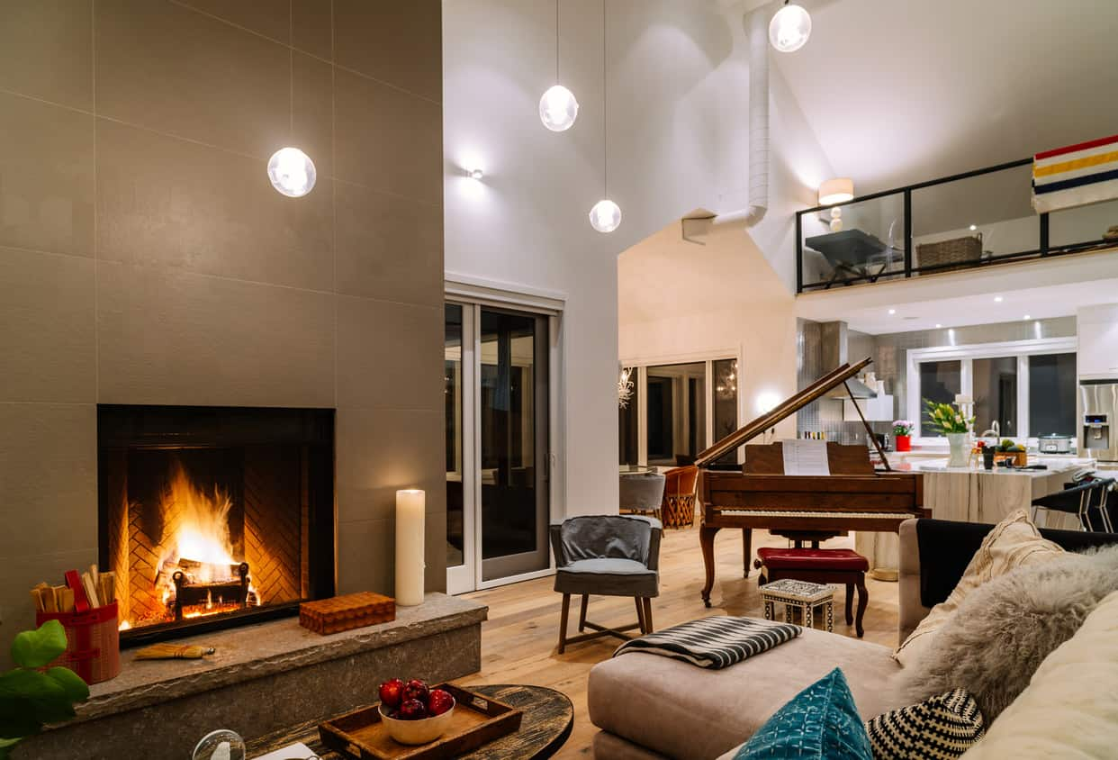 Gorgeous brown and white living room with fireplace, brown furniture and brown grand piano off to the side.
