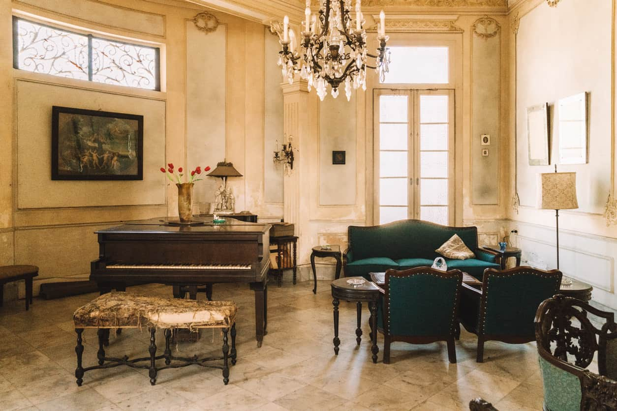 Large formal drawing room with grand piano under the large and stunning chandelier.