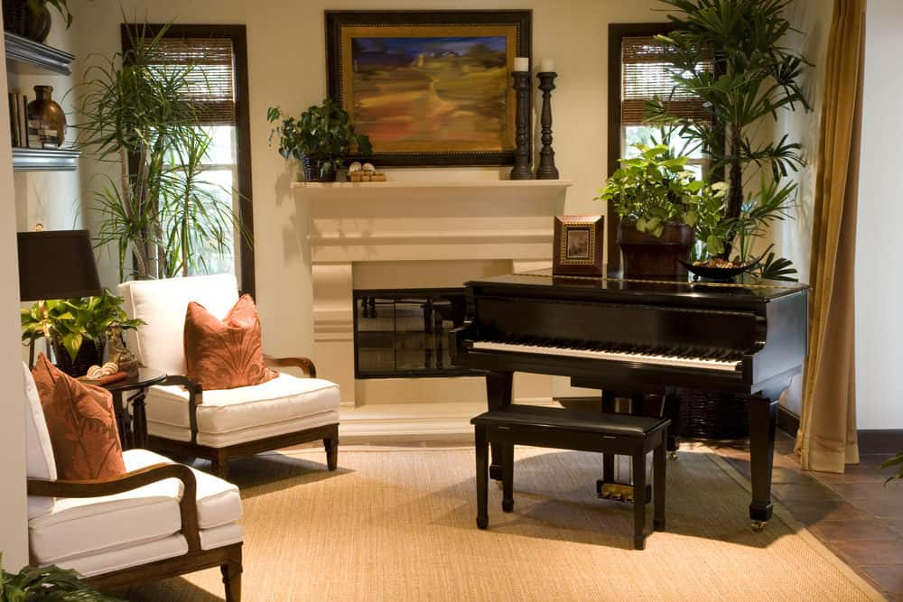Living room with two white accent chairs, fireplace, light beige carpeting and black piano.