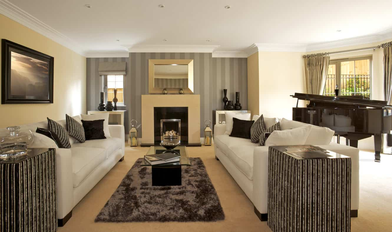 A classy living room with white sofa set and a modish fireplace along with stylish side tables and a grand piano on the side.