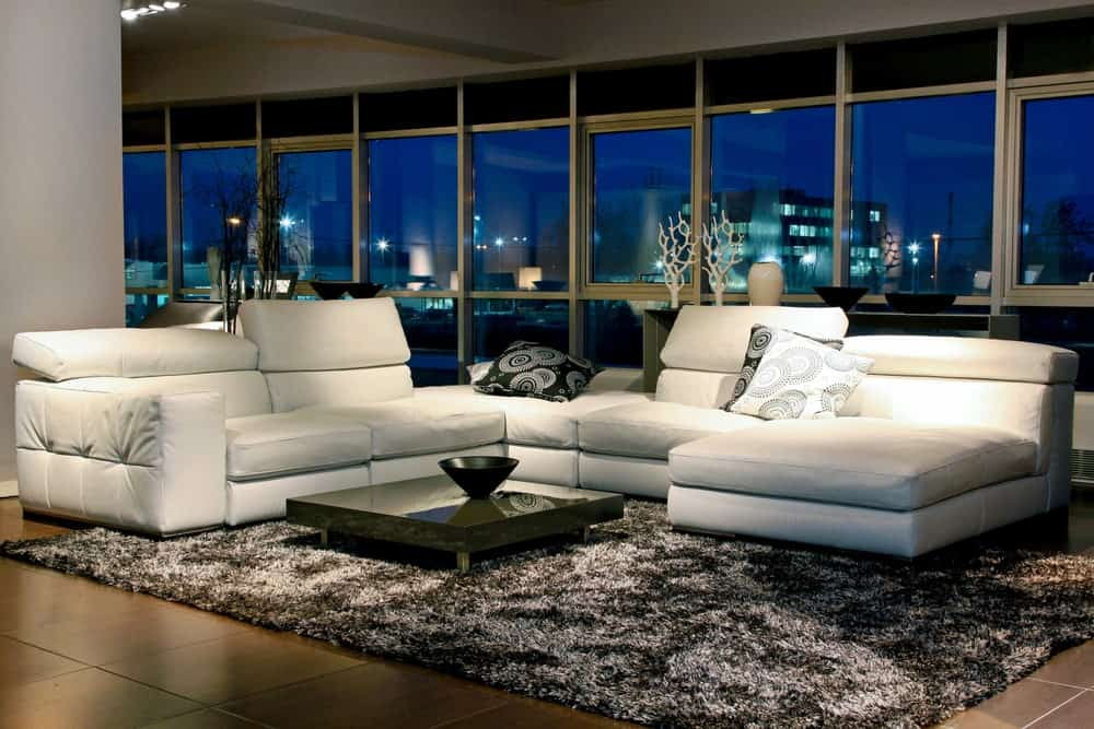 Large modern living room with tiles flooring topped by a stylish rug where the white sofa set and small center table are set. The area is surrounded by glass walls and windows.