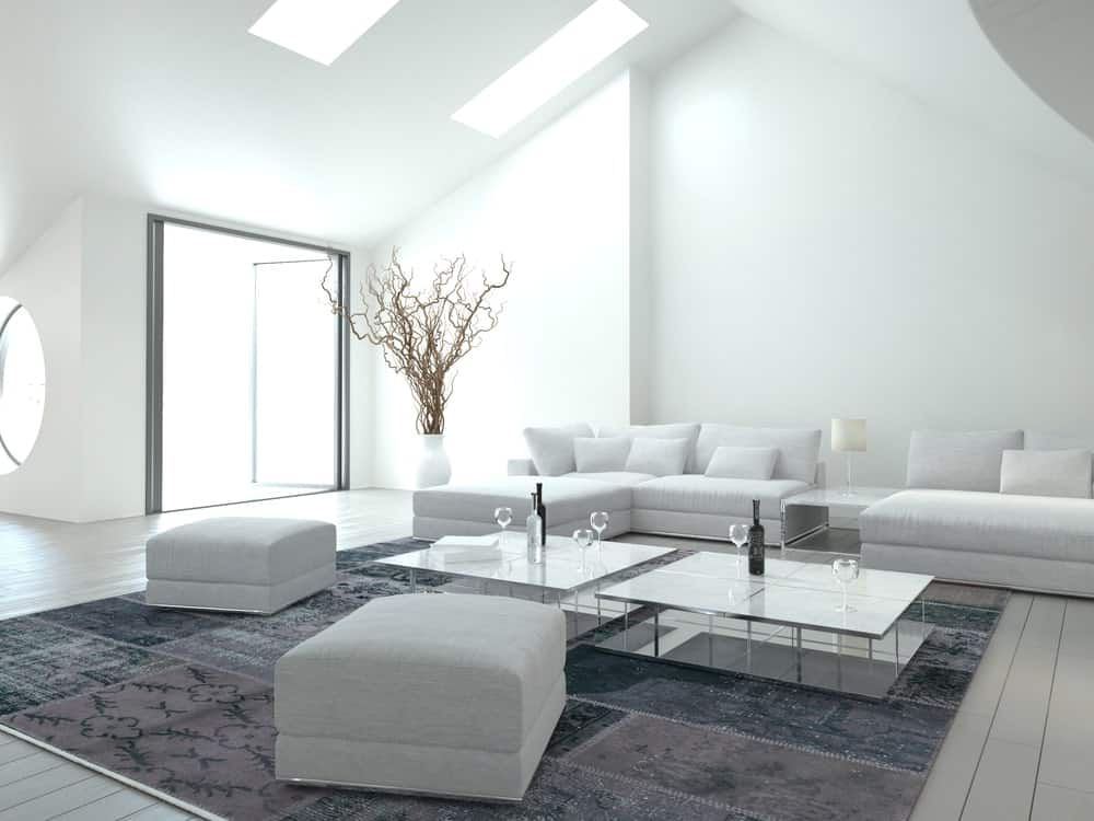 A white living room with gray hardwood flooring topped by a gray rug. The room offers a set of white seats along with a pair of glass top center tables.