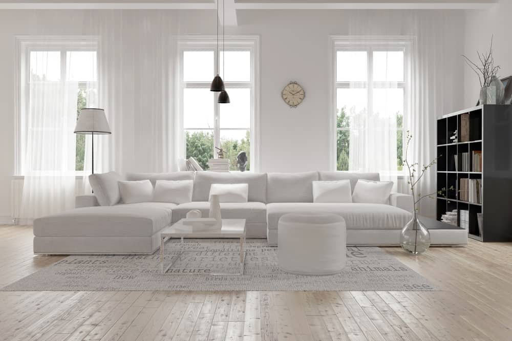 A focused shot at this living room's large white couch set on the room's hardwood flooring.