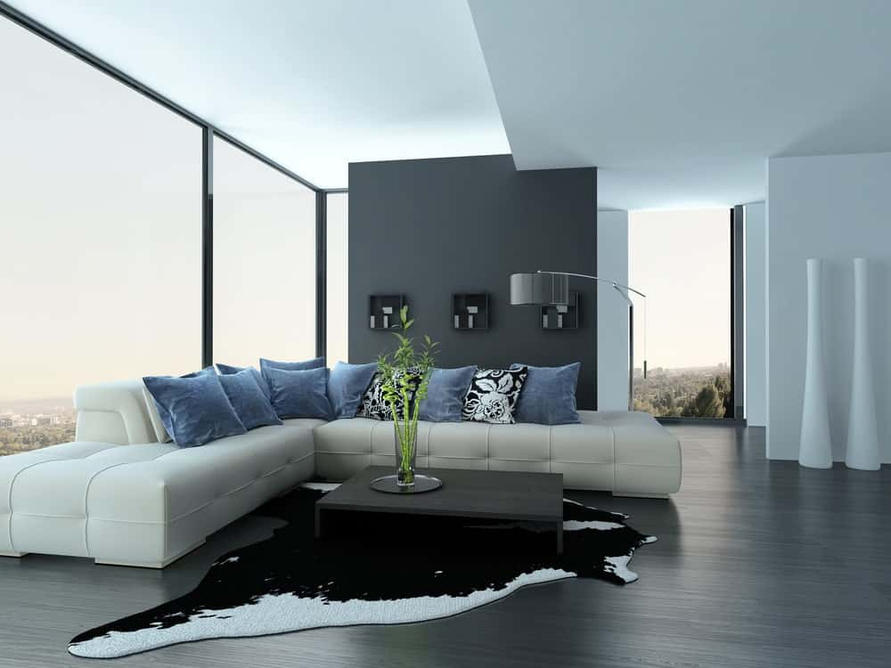 A spacious modern living room with a luxurious white sofa set and a stylish rug. There's a center table and a floor lamp as well. The glass walls offer amazing view of the surroundings.