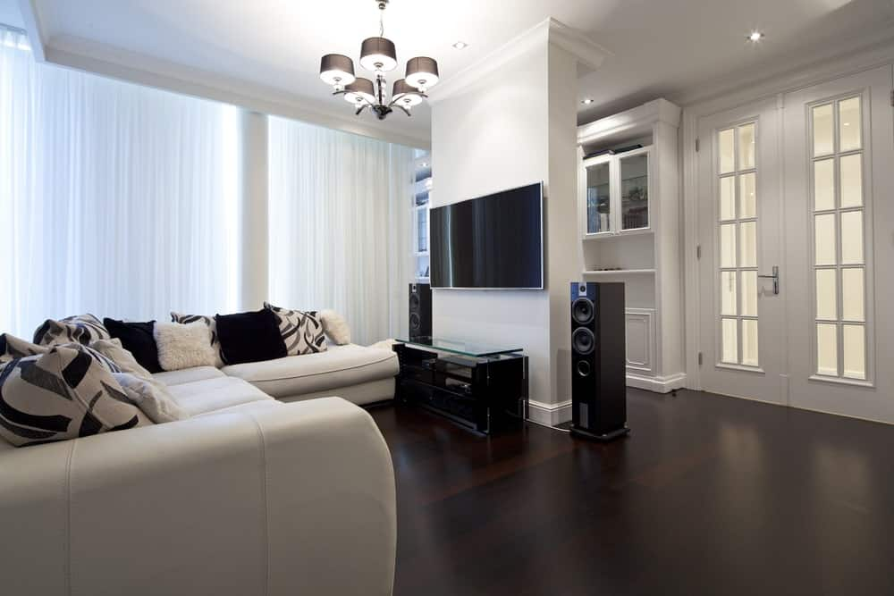 A spacious white living room featuring a white sofa set, a TV on the wall and a gorgeous chandelier.