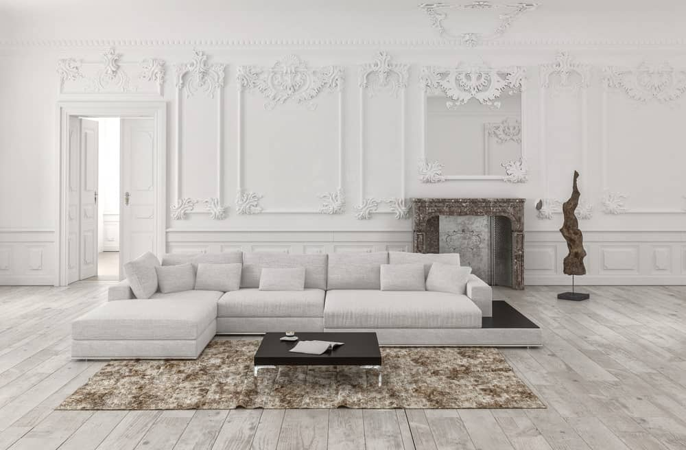This living room boasts white decorated walls that look so elegant. The room offers a white sofa set and a fireplace.