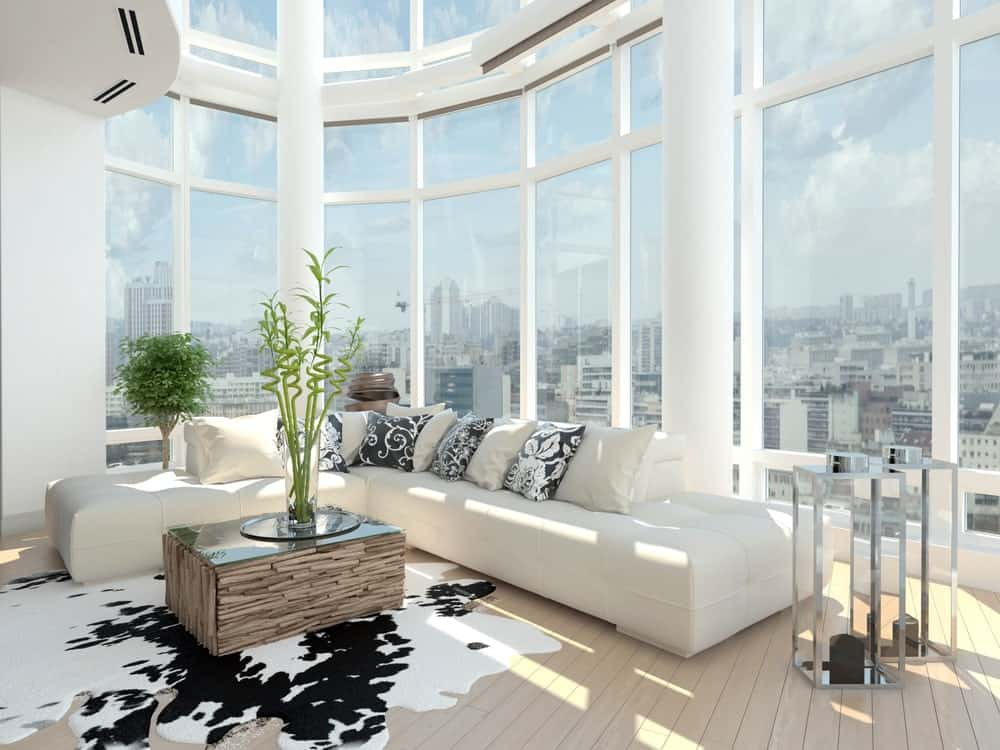 White living room featuring tall glass windows and walls. It also has a tall ceiling and hardwood flooring, together with a white couch and a stylish center table.