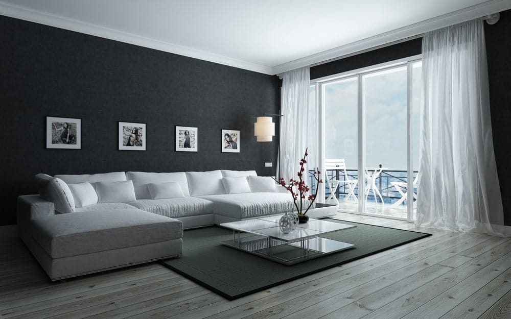 A living room with a black and white color scheme. It features a large white sofa set and a black rug covering the hardwood flooring. There's a doorway leading to a private balcony with a stunning ocean view.
