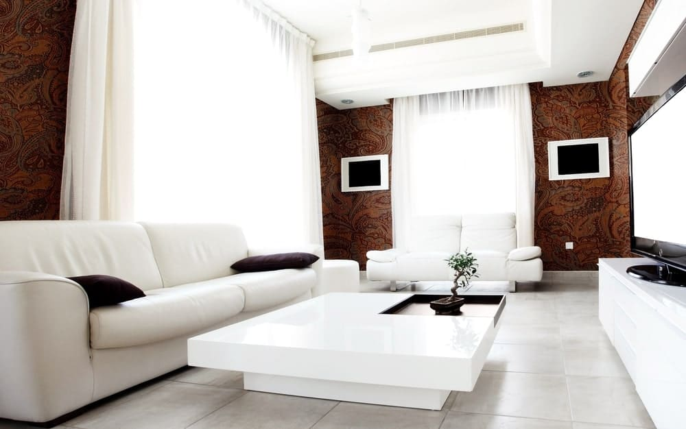 This home boasts a living room with elegant decorated walls along with white seats and a white center table.