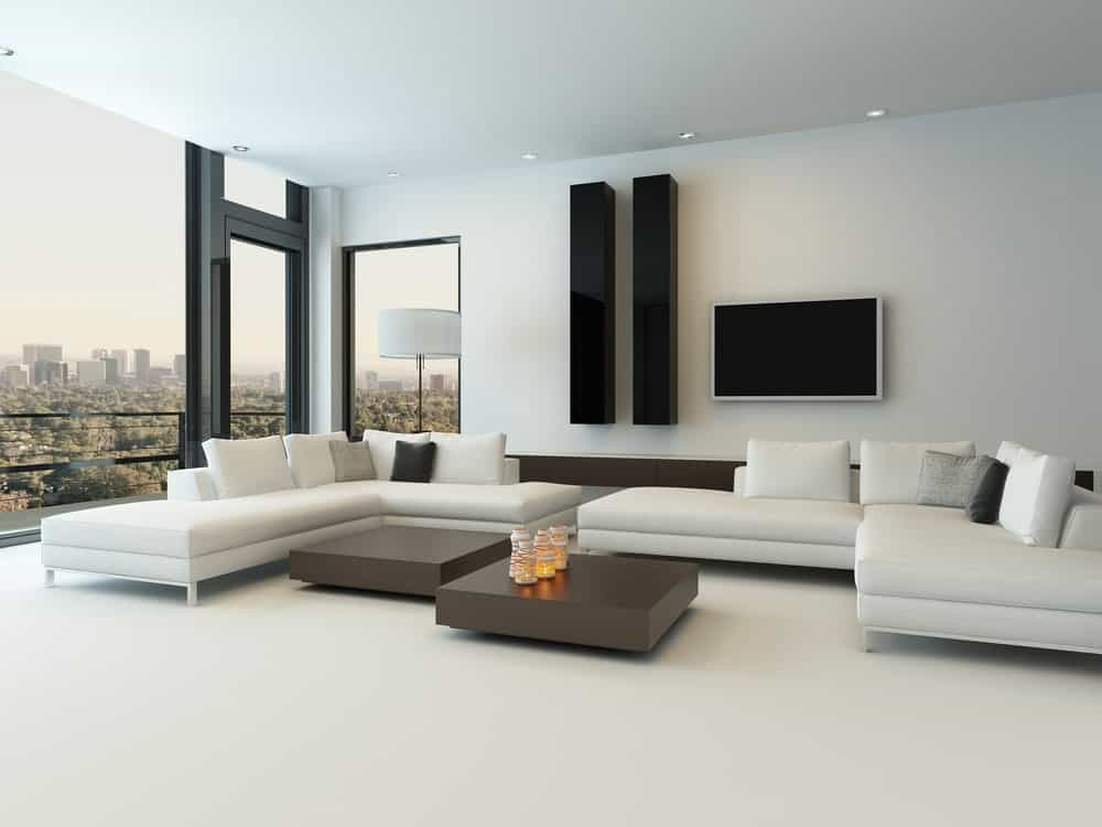 White modern living room featuring white carpet flooring, white walls and a white ceiling. The white couches pair well with the couple of center tables.