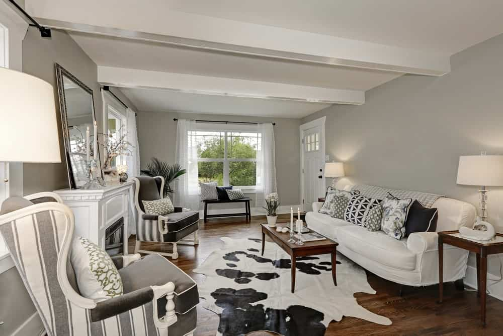A living room with gray walls and hardwood floors. It offers a white couch and a fireplace, along with a stylish rug.